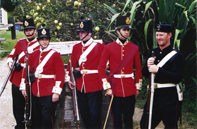 Members wearing red parade tunics and fatigue uniform